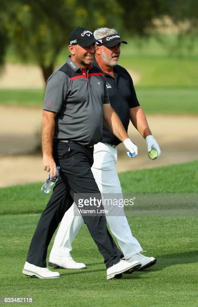 Thomas Bjorn of Denmark and Darren Clarke of NOrthern Ireland walk up the first fairway during the first round of the Omega Dubai Desert Classic at...
