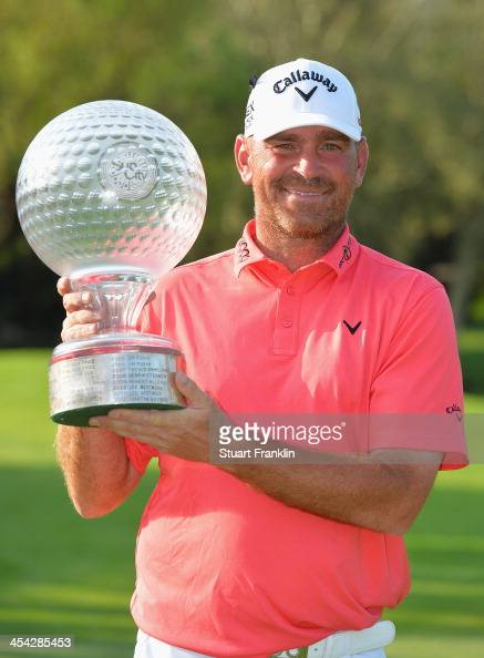 Thomas Bjorn of Denmark holds the trophy after winning the Nedbank Golf Challenge at Gary Player CC on December 8 2013 in Sun City South Africa