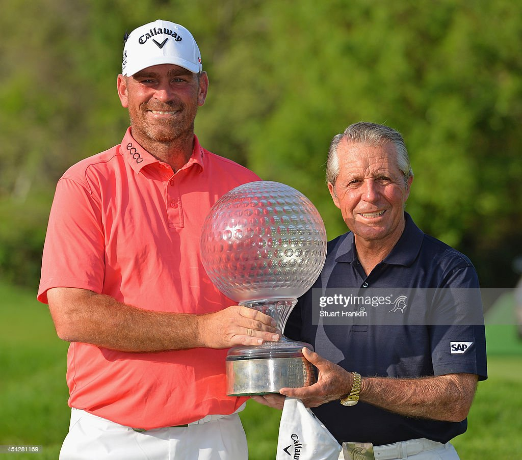 Thomas Bjorn of Denmark holds the trophy with South African golf legend Gary Player, after the Nedbank Golf Challenge at Gary Player CC on December 8, 2013 in Sun City, South Africa.