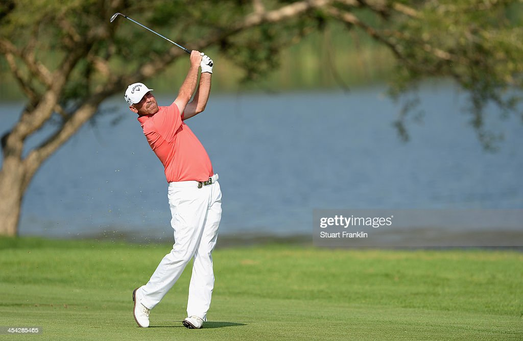 Thomas Bjorn of Denmark plays his approach shot on the 18th hole during the final round of the Nedbank Golf Challenge at Gary Player CC on December 8, 2013 in Sun City, South Africa.
