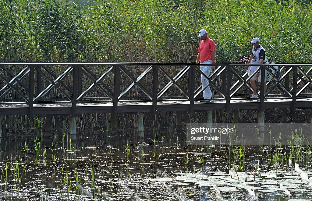 Thomas Bjorn of Denmark walks with his caddie Phil Morby during the final round of the Nedbank Golf Challenge at Gary Player CC on December 8, 2013 in Sun City, South Africa.