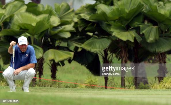 Thomas Bjorn of Team Europe lines for a putt on the 14th hole in the singles draw matches against Team Asia during day three of the EurAsia Cup at...
