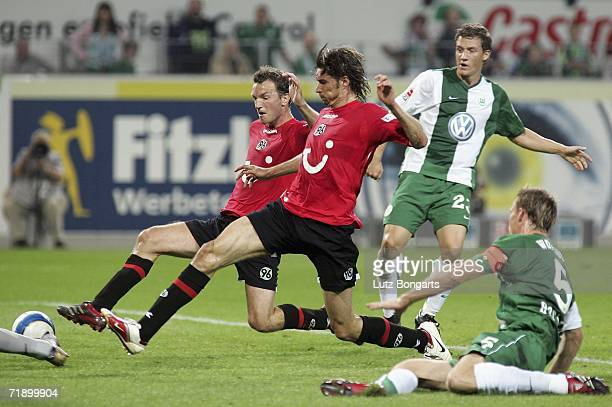 Thomas Brdaric and Arnold Bruggink of Hannover 96 miss a chance at goal during the Bundesliga match between VFL Wolfsburg and Hanover 96 at the...