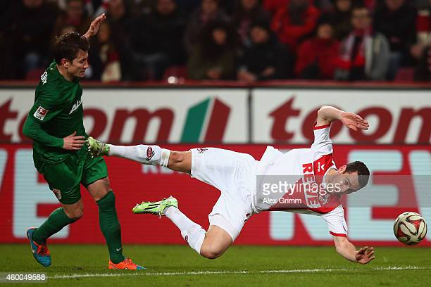 Thomas Broeker of Koeln is challenged by Paul Verhaegh of Augsburg during the Bundesliga match between 1 FC Koeln and FC Augsburg at...