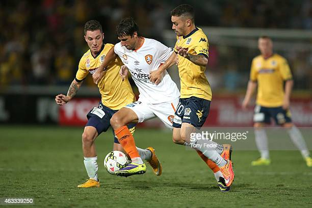 Thomas Broich of the Roar controls the ball betwen Storm Roux and Anthony Caceres of the Mariners during the round 17 ALeague match between the...