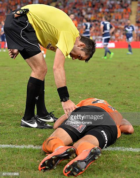 Thomas Broich of the Roar is checked on by referee Jarred Gillett after being taken down in an illegal tackle by Jason Geria of the Victory during...