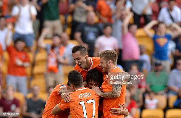 Thomas Broich of the Roar is congratulated by team mates after scoring a goal during the round one ALeague match between the Brisbane Roar and...