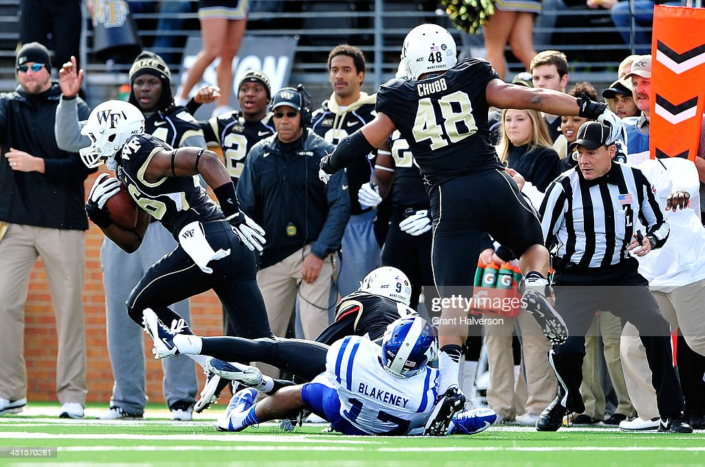 Thomas Brown #26 of the Wake Forest Demon Deacons returns a fumble by Issac Blakeney #17 of the Duke Blue Devils for a touchdown during play at BB&T Field on November 23, 2013 in Winston Salem, North Carolina.