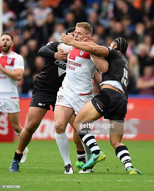 Thomas Burgess of England is tackled by Jason Taumalolo and Martin Taupau of New Zealand Kiwis during the Four Nations match between the England and...