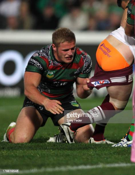 Thomas Burgess of the Rabbitohs pulls on the shorts of a Manly player during the round 23 NRL match between the South Sydney Rabbitohs and the Manly...