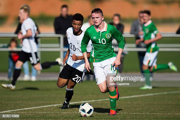 Thomas Byrne of Ireland conducts the ball past Timothy Tillman of Germany during the U18 international friendly match between Ireland and Germany on...
