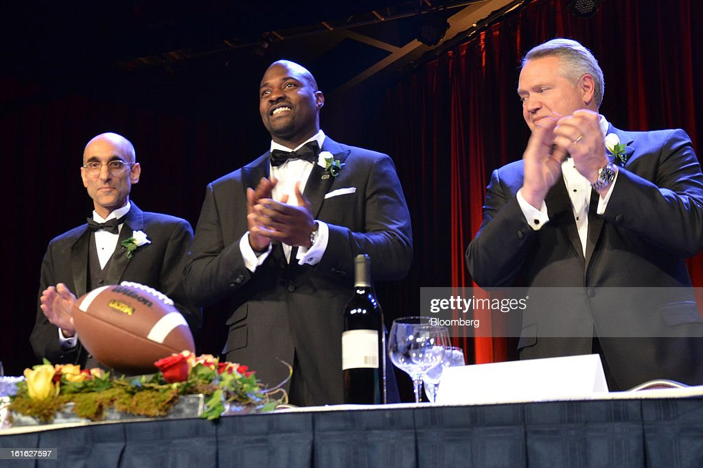 Thomas Catena, medical director at Mother of Mercy Hospital in the Nuba Mountain region of the Sudan, from left, Marcellus Wiley, a host and analyst for ESPN, and Tim Ring, CEO and chairman of C.R. Bard Inc., stand on the dais as honorees at the Ivy Football Association Dinner at the Marriott Marquis in New York, U.S. on Thursday, Feb. 7, 2013. The event brought together alumni who played football for the eight schools in the Ivy League: Brown, Columbia, Cornell, Dartmouth, Harvard, University of Pennsylvania, Princeton and Yale. Photographer: Amanda Gordon/Bloomberg via Getty Images