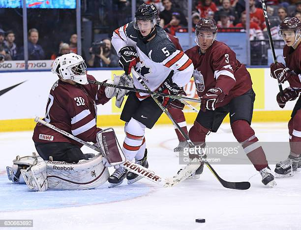 Thomas Chabot of Team Canada barges between Mareks Mitens and Eduards Jansons of Team Latvia during a preliminary game in the 2017 IIHF World Junior...