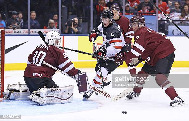 Thomas Chabot of Team Canada skates between Mareks Mitens and Eduards Jansons of Team Latvia during a preliminary game in the 2017 IIHF World Junior...