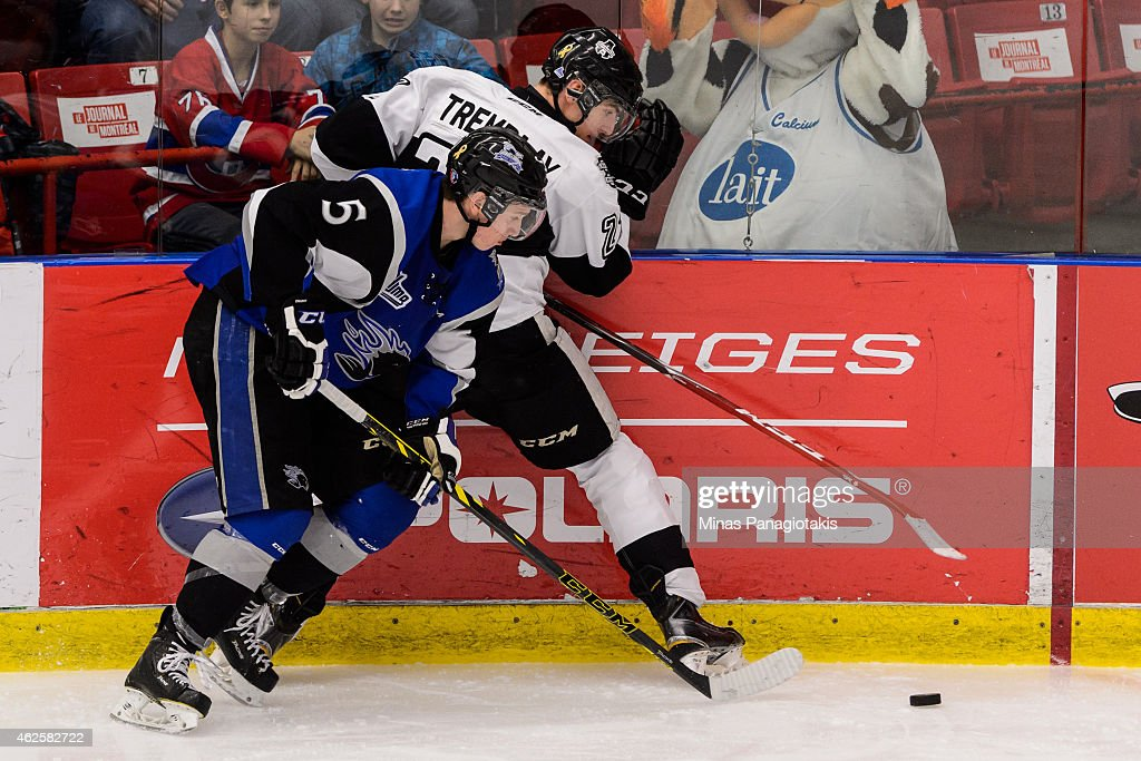 Thomas Chabot #5 of the Saint John Sea Dogs pins Samuel Tremblay #27 of the Blainville-Boisbriand Armada to the boards during the QMJHL game at the Centre Excellence Rousseau on January 31, 2015 in Blainville-Boisbriand, Quebec, Canada. The Blainville-Boisbriand Armada defeated the Saint John Sea Dogs 4-0.