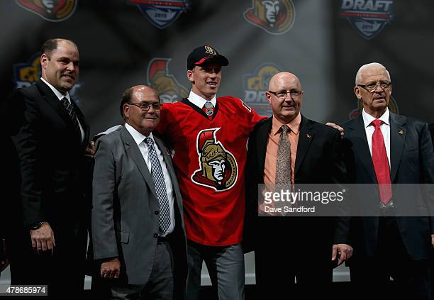Thomas Chabot poses on stage with team personnel after being selected 18th by the Ottawa Senators during Round One of the 2015 NHL Draft at BBT...