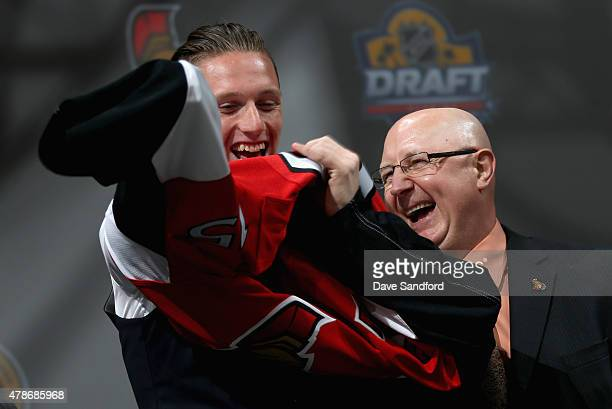 Thomas Chabot puts on his jersey after being selected 18th by the Ottawa Senators during Round One of the 2015 NHL Draft at BBT Center on June 26...