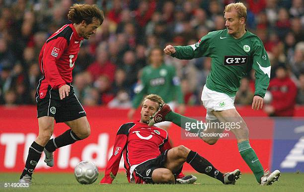 Thomas Christiansen of Hannover 96 plays the ball after teammate Christoph Dabrowski of Hannover tackles Miroslav Karhan of Vfl Wolfsburg during...