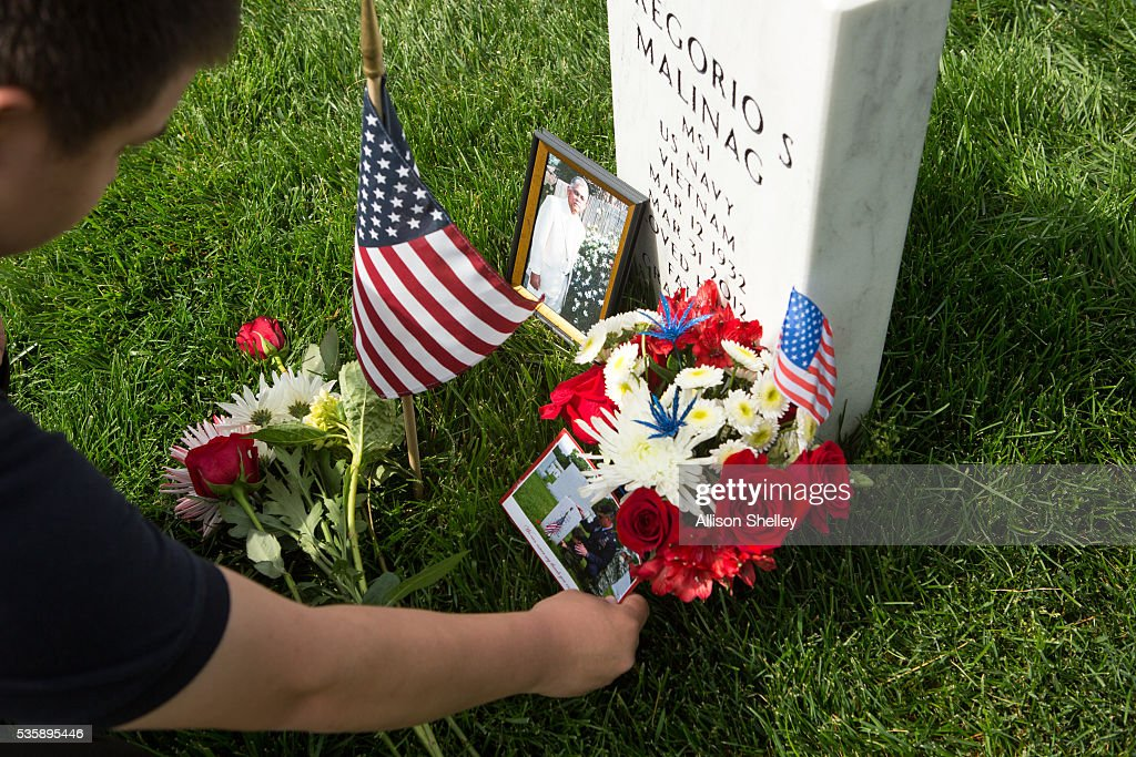 Thomas Cowan, 17, places a flower and photo at the grave of Gregorio S. Malinag, in Section 60, the burial ground for military personnel killed since 2001, at Arlington National Cemetery on May 30, 2016 in Arlington, Virginia. Cowan and his father Tom, who served in the Air Force for 21 years, has been honoring strangers in this manner for many years. Tom's oldest son is also buried at the cemetery. 'It's our way of giving something back,' says Tom, 'and teaching the boys honor and respect.'