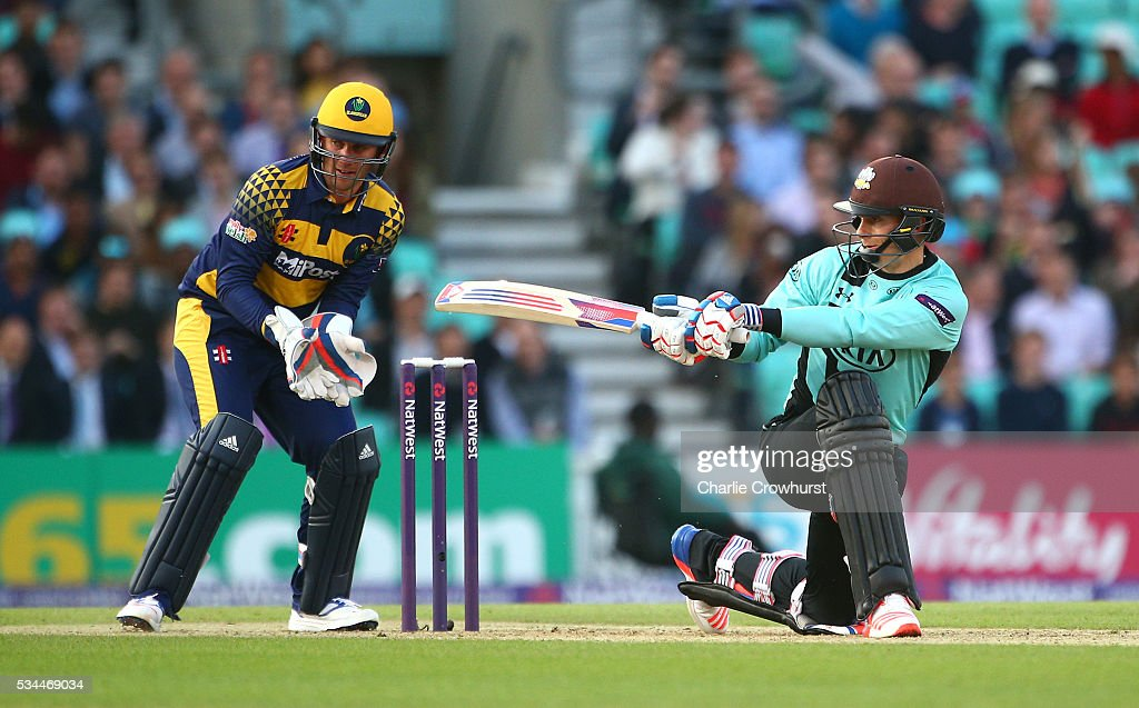 Thomas Curran of Surrey hits out while Chris Cooke (L) of Glamorgan looks on during the Natwest T20 Blast match between Surrey and Glamorgan at The Kia Oval on May 26, 2016 in London, England.