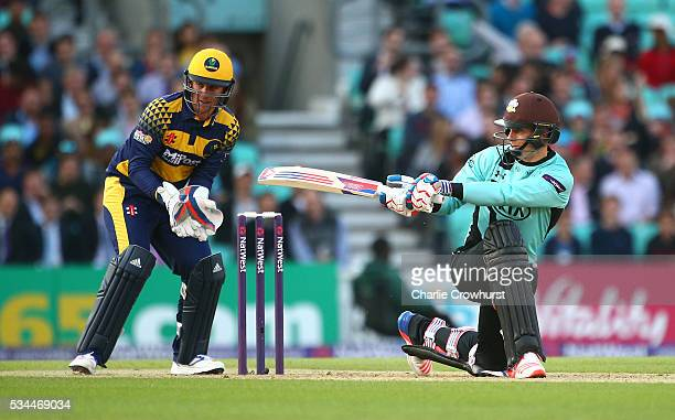 Thomas Curran of Surrey hits out while Chris Cooke of Glamorgan looks on during the Natwest T20 Blast match between Surrey and Glamorgan at The Kia...