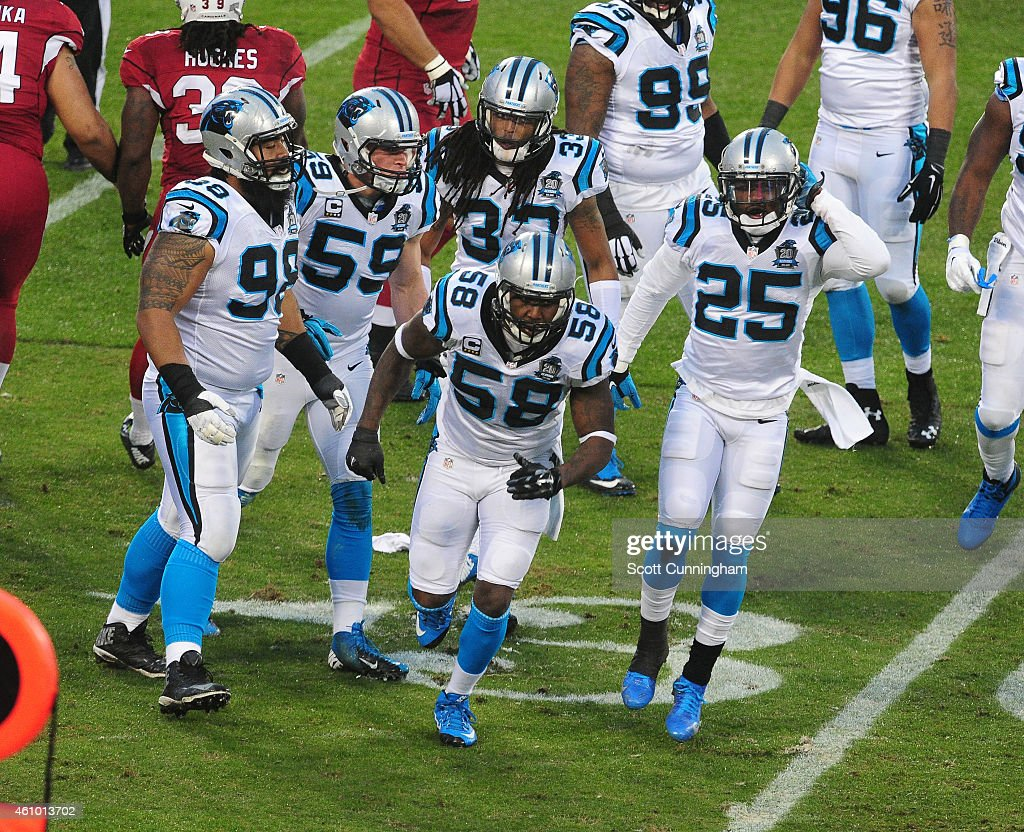 Thomas Davis of the Carolina Panthers heads off the field with teammates after making a stop on third down during the NFC Wild Card Playoff game...