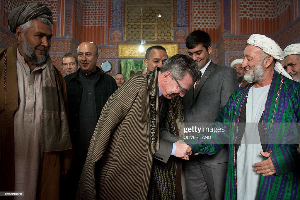 Thomas de Maiziere (Front 2nd L), German Minister of Defence bows as he thanks an Afghan man for the traditional cloak he received while visiting the Blue Mosque in Mazar-i-Sharif, Afghanistan with Mohammed Atta Noor (2nd Row C) ,Governor of the Afghan province Balch,on November 13, 2012. During his two-day surprise visit to Afghanistan De Maiziere visited the German troops and met with his Afghan counterpart for discussions on security issues. AFP PHOTO / POOL/ OLIVER LANG