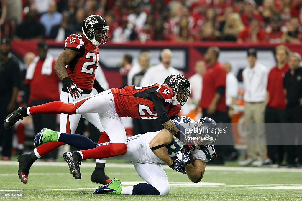 Thomas DeCoud #28 of the Atlanta Falcons tackles Zach Miller #86 of the Seattle Seahawks during the NFC Divisional Playoff Game at Georgia Dome on January 13, 2013 in Atlanta, Georgia.