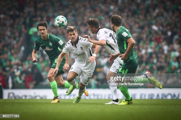 Thomas Delaney of Bremen and Florian Niederlechner of Freiburg compete for the ball during the Bundesliga match between SV Werder Bremen and...