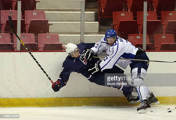 Thomas Di Pauli of the USA Blue Squad is hit by Olli Maata of Team Finland at the USA hockey junior evaluation camp at the Lake Placid Olympic Center...