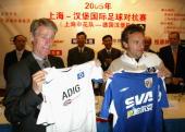 Thomas Doll coach of Germany's Hamburg HSV soccer team exchanges sportswear with Valeri Nepomniatchi coach of Shanghai Shenhua soccer team at a news...
