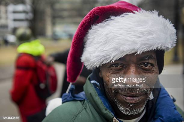 Thomas Dyson who has been homeless in DC for about 15 years sports a Santa hat as volunteers from various organizations hand out gifts of clothes...
