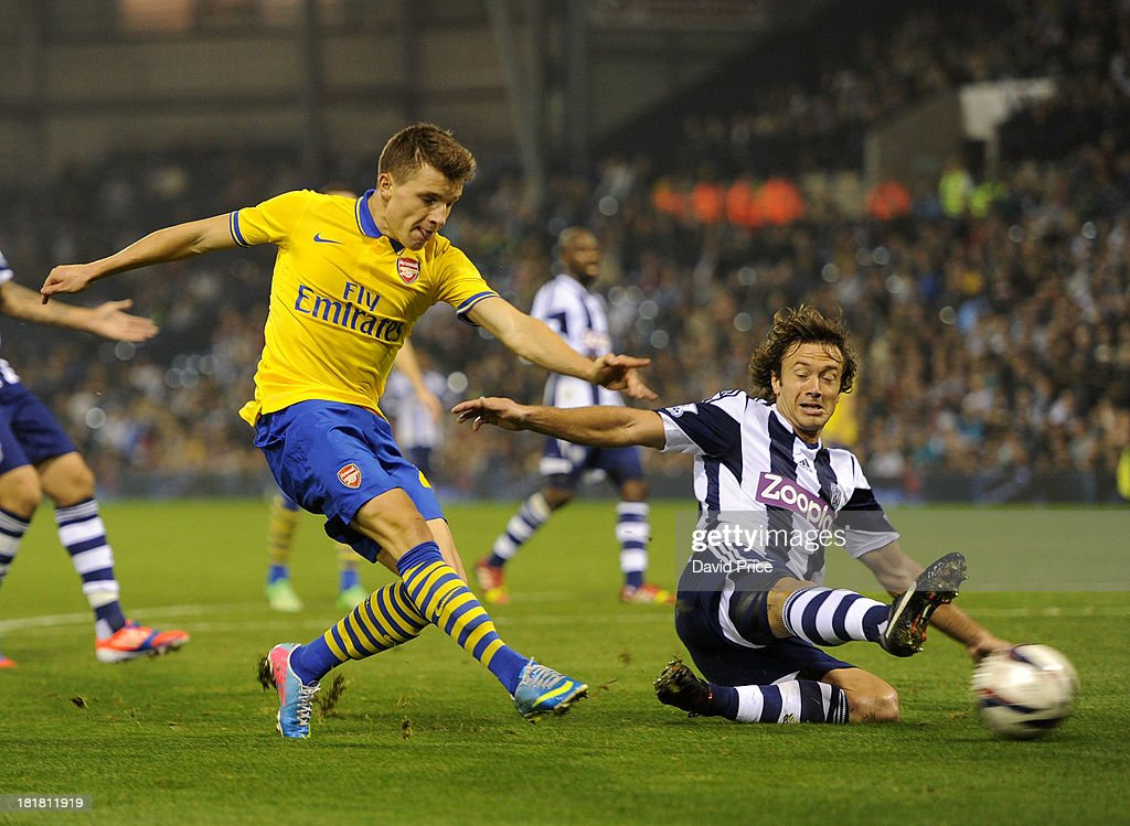 Thomas Eisfeld of Arsenal shoots under pressure from Diego Lugano of West Bromwich Albion during the 3rd round Capital One Cup match between West...