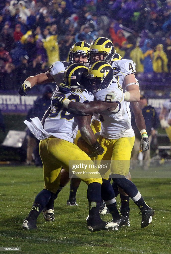 Thomas Gordon #30 of the Michigan Wolverines celebrates with teammates with after catching an intercepcion during overtime play against the Northwestern Wildcats at Ryan Field on November 16, 2013 in Evanston, Illinois.