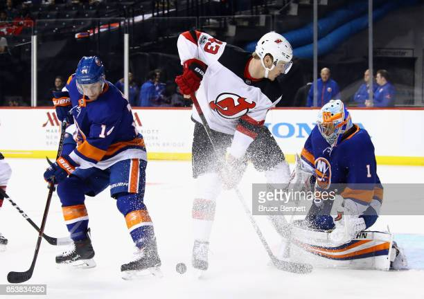 Thomas Greiss and Thomas Hickey of the New York Islanders defend against Ben Thomson of the New Jersey Devils during the first period during a...