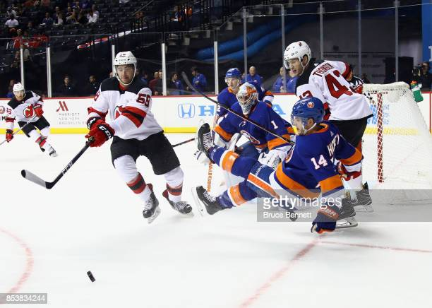 Thomas Greiss and Thomas Hickey of the New York Islanders defend against Kevin Rooney and Ben Thomson of the New Jersey Devils during the first...