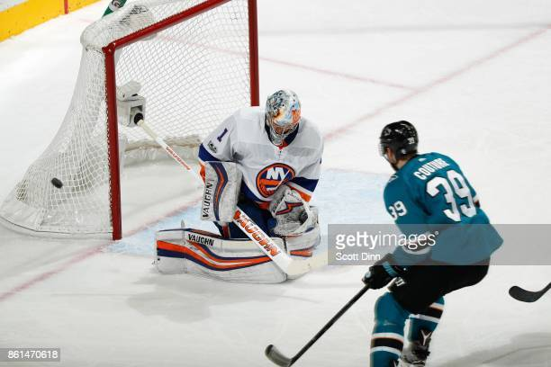 Thomas Greiss of the New York Islanders deflects the puck as Logan Couture of the San Jose Sharks looks at SAP Center on October 14 2017 in San Jose...