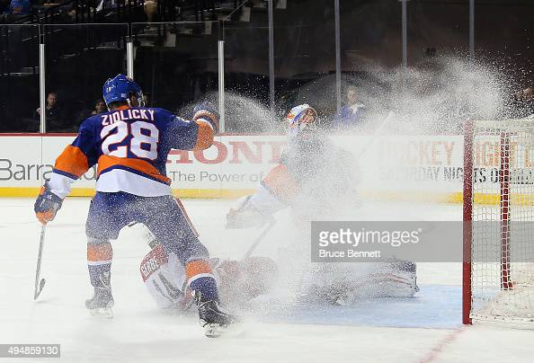 Thomas Greiss of the New York Islanders is covered by a blast of ice as Marek Zidlicky trips up Nathan Gerbe of the Carolina Hurricanes during the...