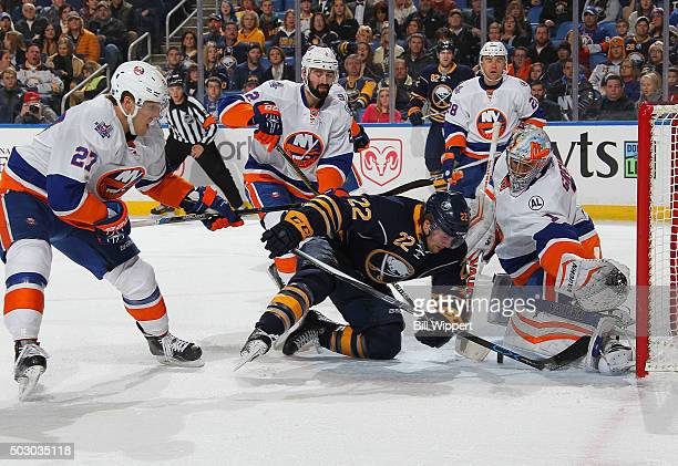 Thomas Greiss of the New York Islanders makes a save while Johan Larsson of the Buffalo Sabres gets cross checked to the ice by Anders Lee Lee...
