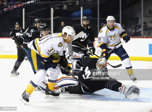 Thomas Greiss of the New York Islanders makes the first period save as Cody McLeod of the Nashville Predators looks for the rebound at the Barclays...
