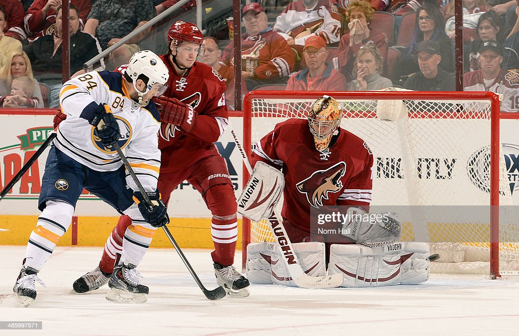 <a gi-track='captionPersonalityLinkClicked' href=/galleries/search?phrase=Thomas+Greiss&family=editorial&specificpeople=695275 ng-click='$event.stopPropagation()'>Thomas Greiss</a> #1 of the Phoenix Coyotes makes a save as Philip Varone #84 of the Buffalo Sabres and <a gi-track='captionPersonalityLinkClicked' href=/galleries/search?phrase=Oliver+Ekman-Larsson&family=editorial&specificpeople=5894618 ng-click='$event.stopPropagation()'>Oliver Ekman-Larsson</a> #23 of the Coyotes battle in front of the net during the third period at Jobing.com Arena on January 30, 2014 in Glendale, Arizona.