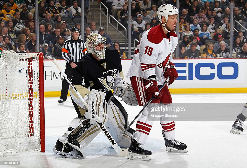 <a gi-track='captionPersonalityLinkClicked' href=/galleries/search?phrase=Thomas+Greiss&family=editorial&specificpeople=695275 ng-click='$event.stopPropagation()'>Thomas Greiss</a> #1 of the Pittsburgh Penguins defends the net in front of <a gi-track='captionPersonalityLinkClicked' href=/galleries/search?phrase=David+Moss+-+Jugador+de+hockey+sobre+hielo&family=editorial&specificpeople=6928499 ng-click='$event.stopPropagation()'>David Moss</a> #18 of the Arizona Coyotes at Consol Energy Center on March 28, 2015 in Pittsburgh, Pennsylvania.