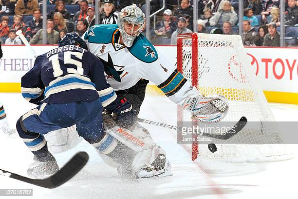 Thomas Greiss of the San Jose Sharks throws the puck away from Derek Dorsett of the Columbus Blue Jackets during the first period on January 14 2012...