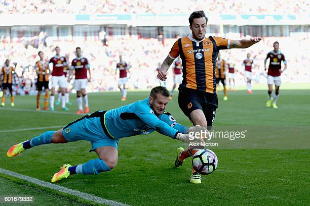 Thomas Heaton of Burnley dives for the ball while Ryan Mason of Hull City attempts to get there first during the Premier League match between Burnley...