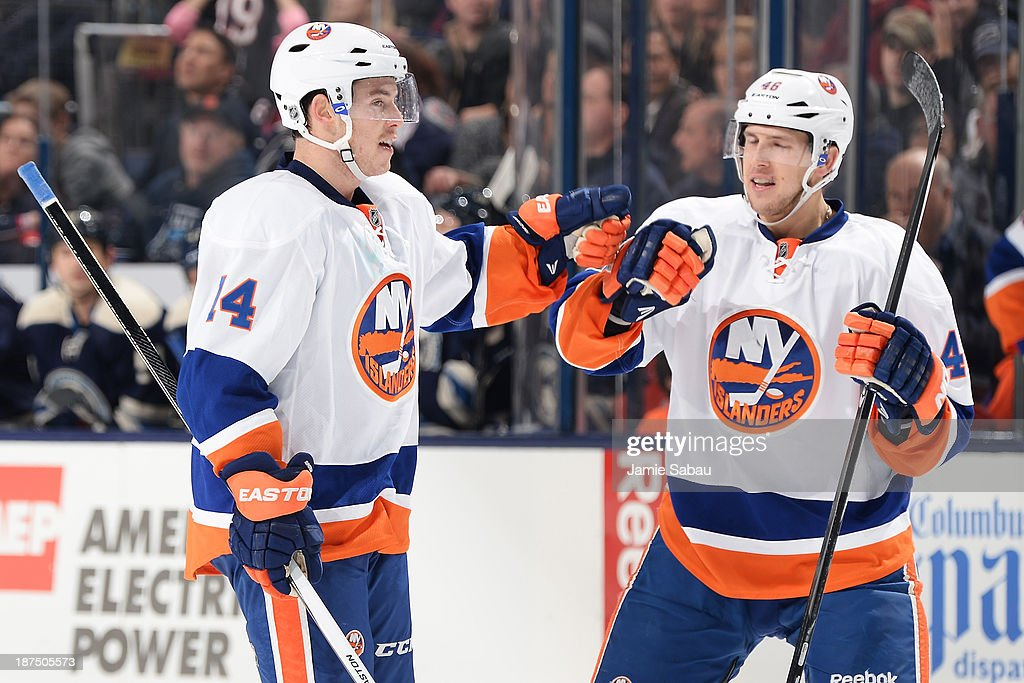 Thomas Hickey #14 of the New York Islanders celebrates with teammate Matt Donovan #46 of the New York Islanders after scoring a second period goal against the New York Islanders on November 9, 2013 at Nationwide Arena in Columbus, Ohio.