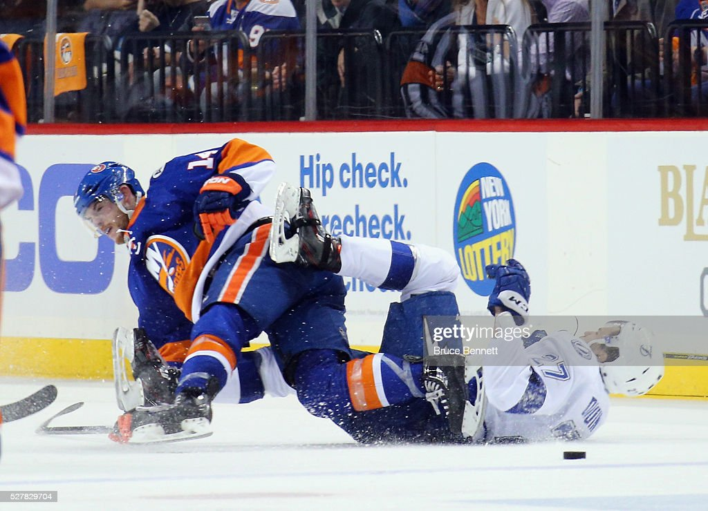 Thomas Hickey #14 of the New York Islanders checks <a gi-track='captionPersonalityLinkClicked' href=/galleries/search?phrase=Jonathan+Drouin+-+Ice+Hockey+Player&family=editorial&specificpeople=10884241 ng-click='$event.stopPropagation()'>Jonathan Drouin</a> #27 of the Tampa Bay Lightning during the second period in Game Three of the Eastern Conference Second Round during the 2016 NHL Stanley Cup Playoffs at the Barclays Center on May 03, 2016 in the Brooklyn borough of New York City.