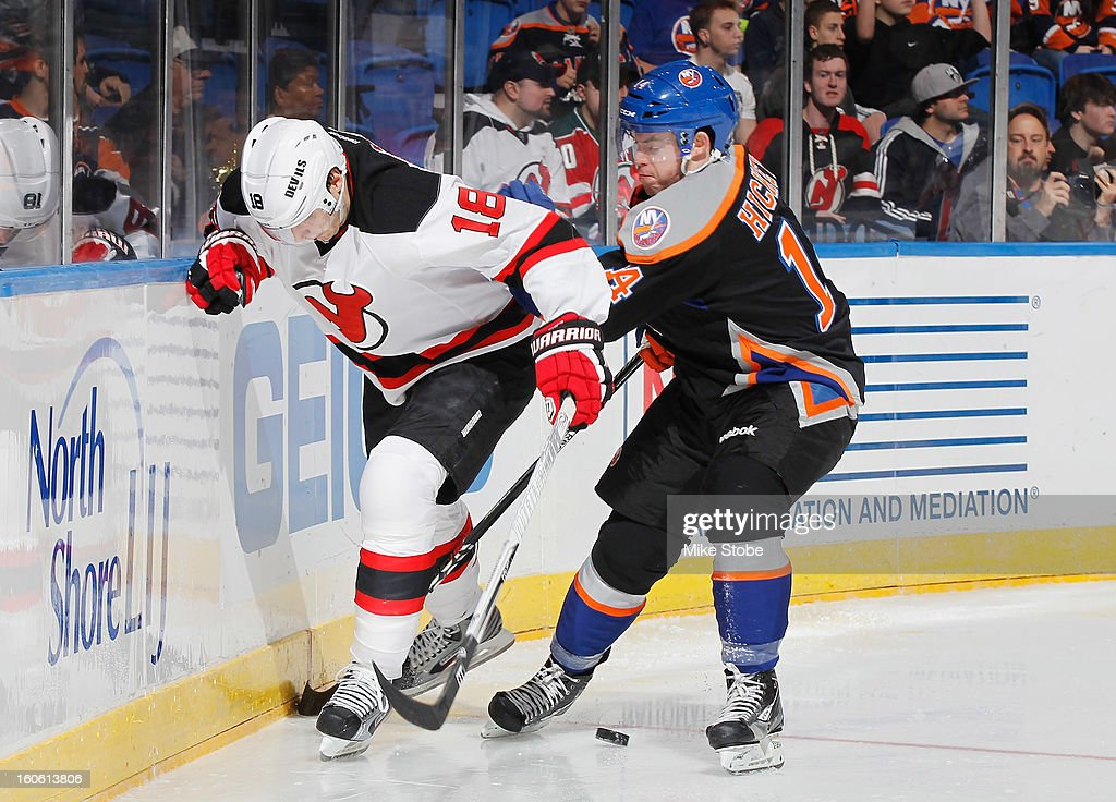 Thomas Hickey #14 of the New York Islanders fights for the puck against <a gi-track='captionPersonalityLinkClicked' href=/galleries/search?phrase=Steve+Bernier&family=editorial&specificpeople=557040 ng-click='$event.stopPropagation()'>Steve Bernier</a> #18 of the New Jersey Devils at Nassau Veterans Memorial Coliseum on Febuary 3, 2013 in Uniondale, New York. The Devils defeated the Islanders 3-0.