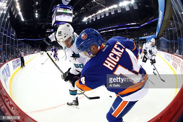 Thomas Hickey of the New York Islanders handles the puck against Chris Tierney of the San Jose Sharks in the first period at Barclays Center on...