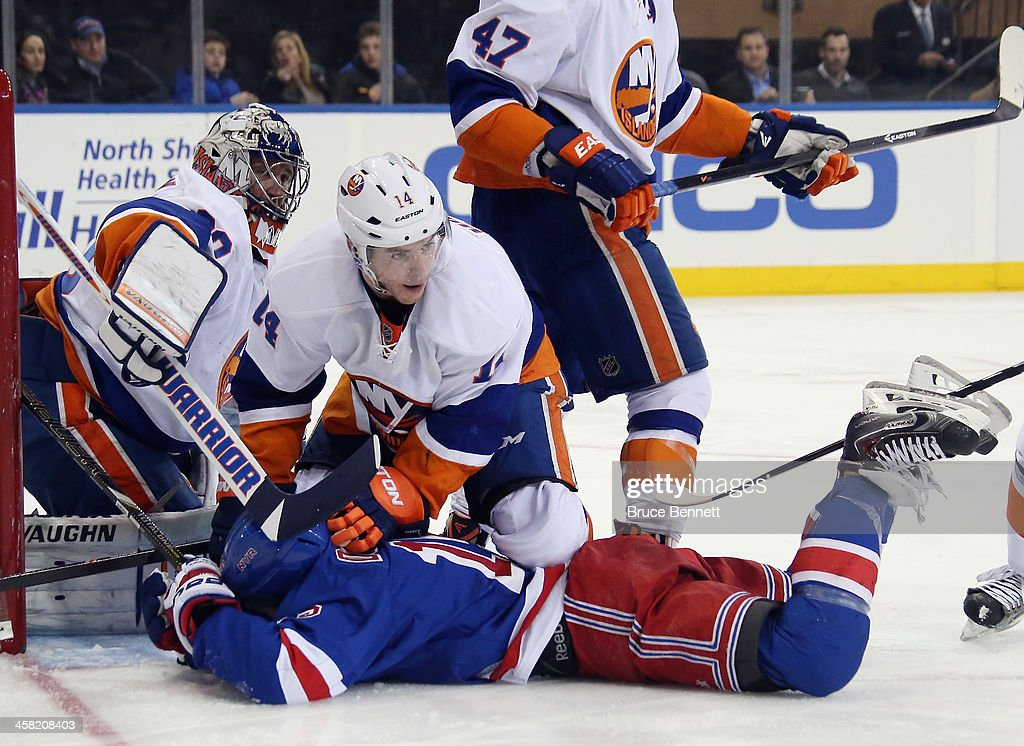 Thomas Hickey #14 of the New York Islanders holds <a gi-track='captionPersonalityLinkClicked' href=/galleries/search?phrase=Derek+Dorsett&family=editorial&specificpeople=4306277 ng-click='$event.stopPropagation()'>Derek Dorsett</a> #15 of the New York Rangers on the ice at Madison Square Garden on December 20, 2013 in New York City. The Islanders defeated the Rangers 5-3.
