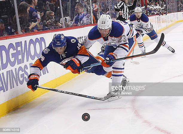 Thomas Hickey of the New York Islanders is hit by Iiro Pakarinen of the Edmonton Oilers during the first period at the Barclays Center on February 7...